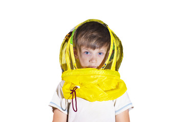 A boy in a yellow mask from bees looks at the camera in the studio, on an isolated background.