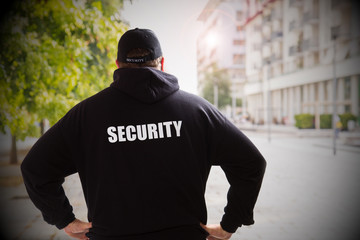 security man in a sunny day checking the city