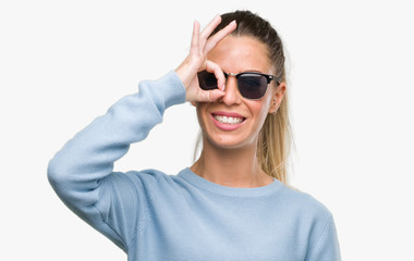 Beautiful young woman wearing sunglasses and ponytail with happy face smiling doing ok sign with hand on eye looking through fingers