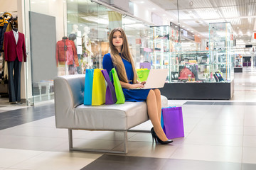 Woman in mall doing online shopping with laptop