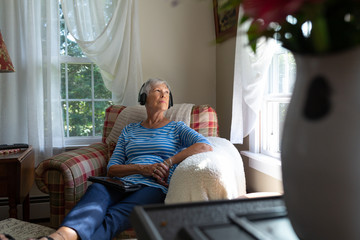 Senior Woman Listening to Podcast with Headphones