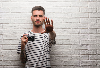 Young man holding vintage camera standing over white brick wall with open hand doing stop sign with serious and confident expression, defense gesture