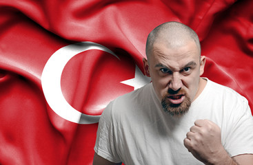 Angry man against flag of Turkey