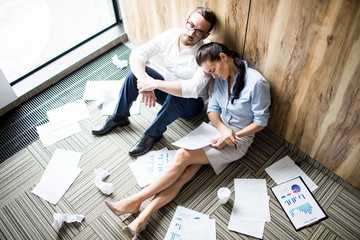 Exhausted young colleagues with papers napping by wall on the floor during work