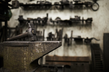 Heavy hammer on iron anvil and set of handtools of blacksmith on background