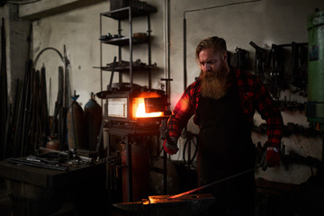 Bearded professional blacksmith with hammer forging hot end of iron workpiece on anvil