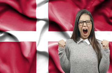 Ecstatic woman holidng fists and screaming against flag of Denmark