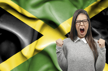 Ecstatic woman holidng fists and screaming against flag of Jamaica