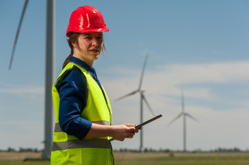 Serious successful young female engineer in a green vest and red hard hat designing a plan against a background of windmills