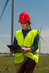 Portrait of a serious successful young female engineer in a green vest and red hard hat designing a plan against a background of windmills