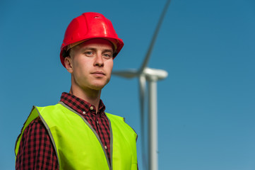 Portrait of a serious ambitious engineer wearing red hard hat against the backdrop of a windmill and a blue sky.