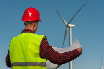 Rear view of unknown male engineer in a green waistcoat with red helmet with engineering plans against the background of windmills and the blue sky