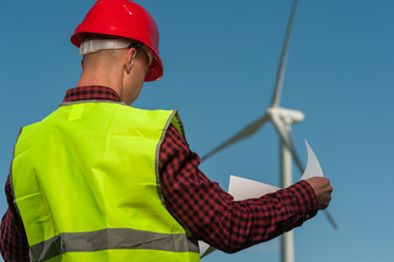 Concept of alternative energy. Rear view man engineer in green vest and helmet against windmills on blue sky