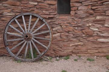 Wagaon Wheel Leaning On Stone Hut