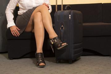 Frau im Minirock und Koffer sitz auf dem Sofa und wartet