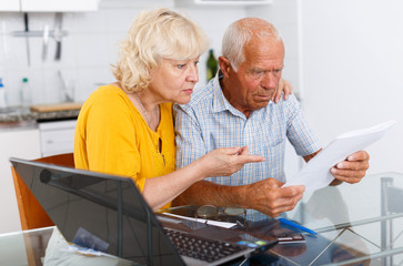 Unhappy senior man and woman with financial documents near laptop