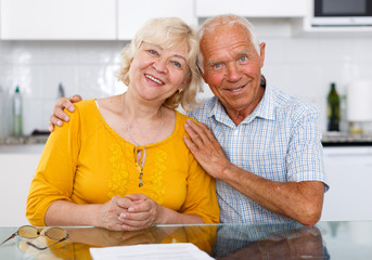 Positive elderly family couple sitting at kitchen table