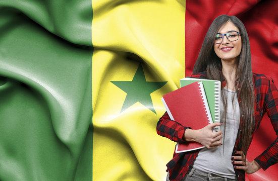 Happy female student holdimg books against national flag of Senegal