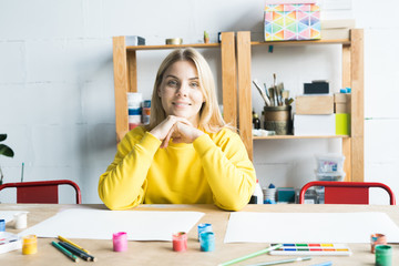 Portrait of smiling young woman sitting at the table in art class and waiting for her pupils