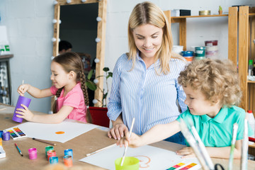 Smiling young teacher in art studio helping children in painting