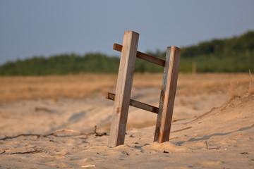 Drewniaana drabinka (płotek) na środku suchego, piaszczystego terenu, przysypana piaskiem, w...