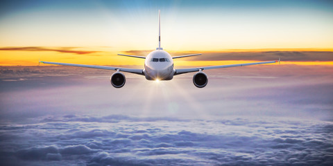 Commercial airplane flying above dramatic clouds. Wall mural