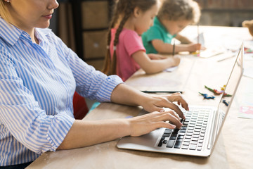 Side view of young mother sitting and typing on laptop while her children drawing at the table