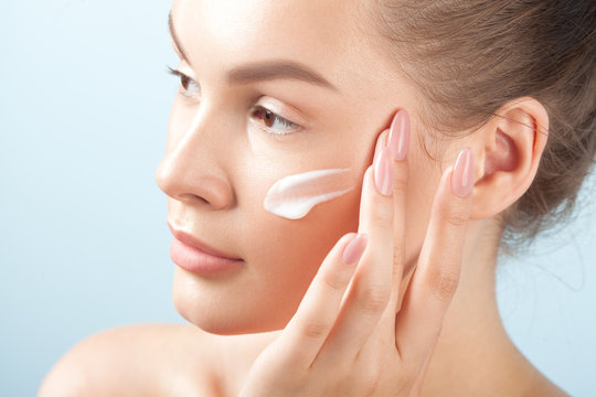 Young beautiful woman applies cream on clean perfect skin