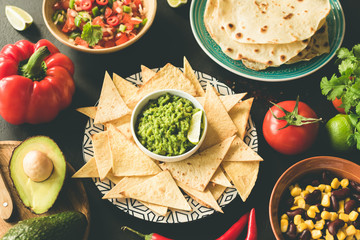 Mexican food selection Guacamole Salsa Nachos Beans on Black Concrete Background. Top view, Toned image