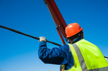 Electricians repairing wire of the power line