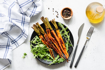 Roasted carrots and fresh green vegetarian salad. Top view. Healthy vegan salad on black plate