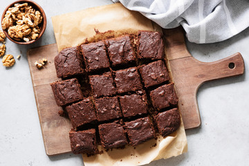 Wall Murals Dessert Chocolate brownie squares with walnuts on cutting board, top view, horizontal composition. Flat lay food