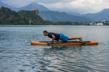 young man exercising on paddle board at the lake
