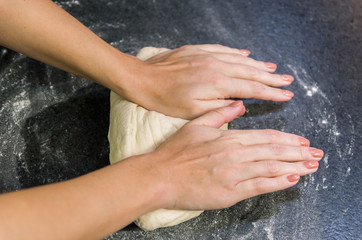 Woman preparing pizza dough on black granite table