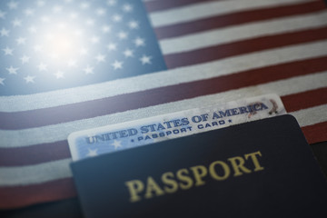 Passport card of USA covered by  International American classic Passport on US Flag. Diagonal view. Light flare effect.