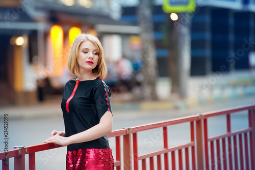 656dc83c88 A blond girl in a red skirt and a black blouse stands on a city street in  the evening. City fashion.