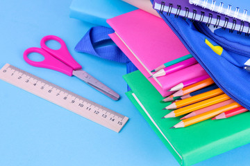 Many multi-colored school supplies falling out of a blue school backpack on a bright blue background Wall mural