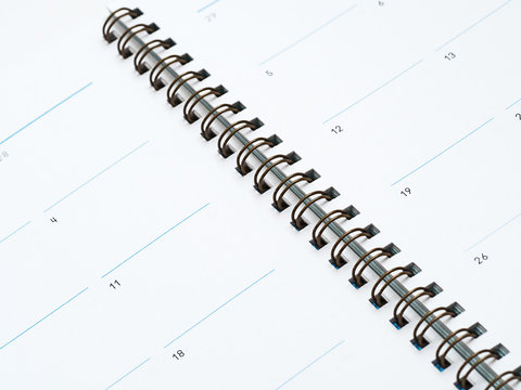 Closeup of partial pages of a spiral bound date book or calendar, with the metal binding spiral running diagonally through the image
