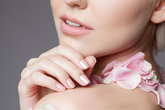 Close-up attractive sensual face of beautiful woman. Macro. Floral petals on her neck. Pink manicure