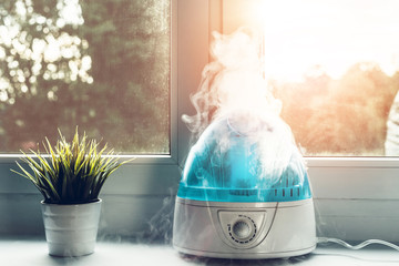 Air humidifier during work. The white humidifier moistens dry air. Improving the comfort of living in the home, apartment. Improving the well-being of people.