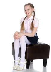 Girl schoolgirl with long pigtails sitting on the couch.