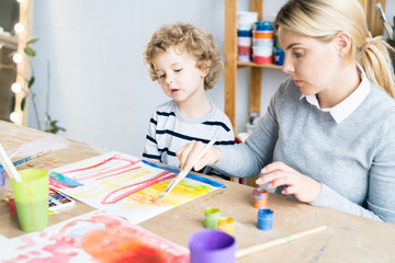 Little boy looking at how teacher helping him to paint a picture in art lesson