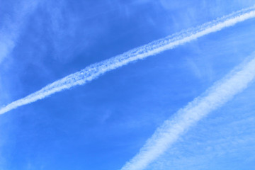 Condensation traces from an airplane in the sky. View diagonally. Close-up. Background. Texture.