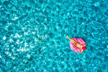 Aerial view of slim young woman swimming on the donut swim ring in the transparent blue sea at bright day. Tropical aerial landscape with girl, clear water in Spain. Top view.Summer travel and holiday
