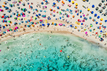 Aerial view of sandy beach with colorful umbrellas, swimming people in sea bay with transparent blue water in sunny morning in summer. Travel in Mallorca, Balearic islands, Spain. Top view. Landscape
