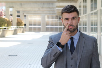 Businessman picking his nose in office space
