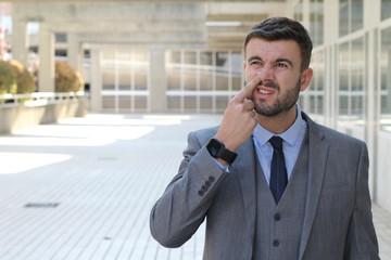 Businessman removing dried nasal secretions