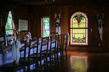 Intimate Wedding Reception Table Setting with White Table Cloth in a Wood Panel Restaurant Room with Stained Glass Window and Chandelier
