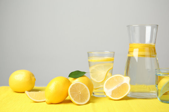 Composition with lemon water and fresh fruits on table