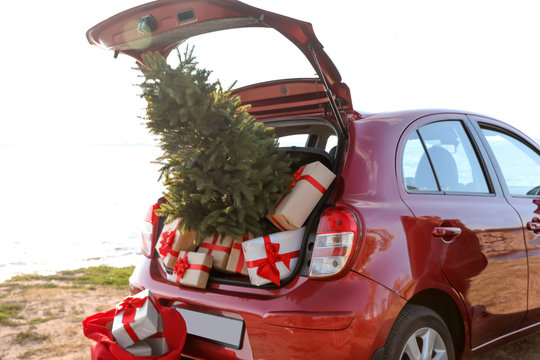 Red car with gift boxes and Christmas tree on beach. Santa Claus delivery